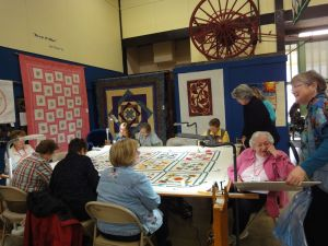 This photo captures the essence of hand quilting at a frame.  Quilting & Talking...