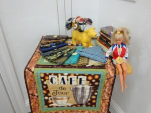 Fat quarters from the Fat Quarter Queen (every year at PIQF Debby buys me a dozen new fat quarters) and Sporty Barbie wearing a 1st Place medal I won in a 10k race years ago...a table topper made by Ann Pfrender and a cow with yoyo flowers...