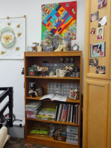 These shelving units and cupboard have all my longarm tools, reference books, thread, and quilts stored in them